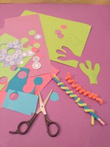 5. Cut dots out of coloured paper, twist pipe cleaners around pencil, cut out 2 hands.