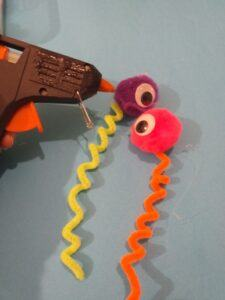 15. Hot wax glue the curled pipe cleaner on to pom pom balls with glued on eyes.