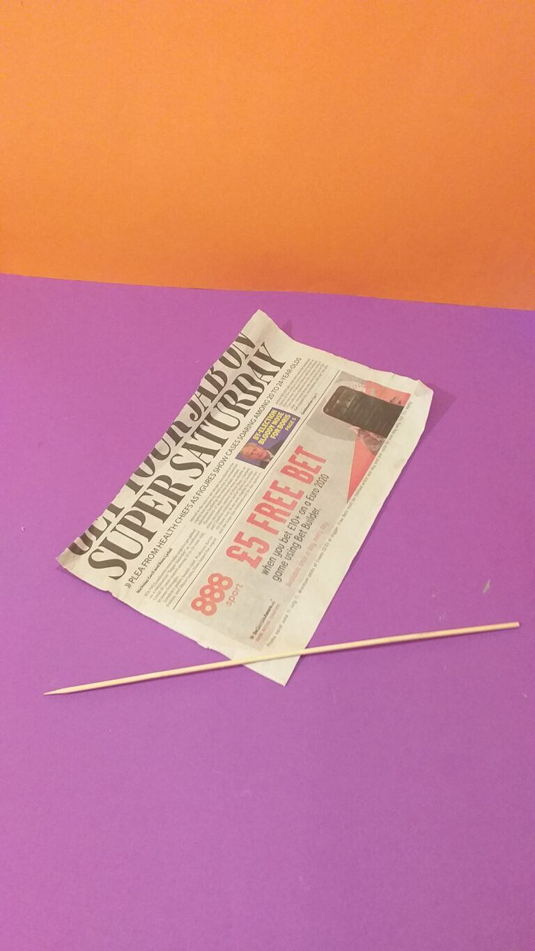 1) Half a sheet of newspaper, take skewer and roll from the corner tightly, but loose enough for stick to manouver.. Hold tight and don't let go.