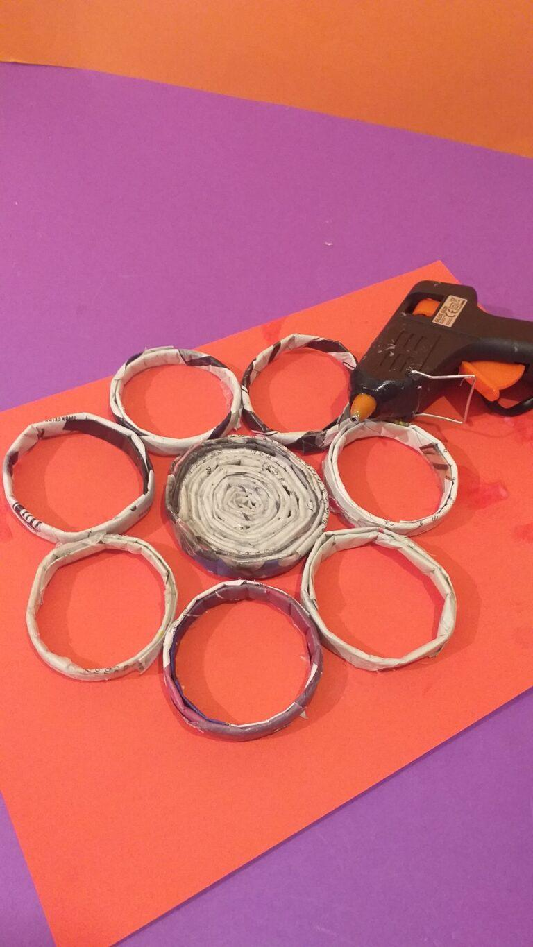 18) Place smaller rings around the base as shown and glue together with the glue gun. You may need to hold till they adhere, be careful as wax is hot.